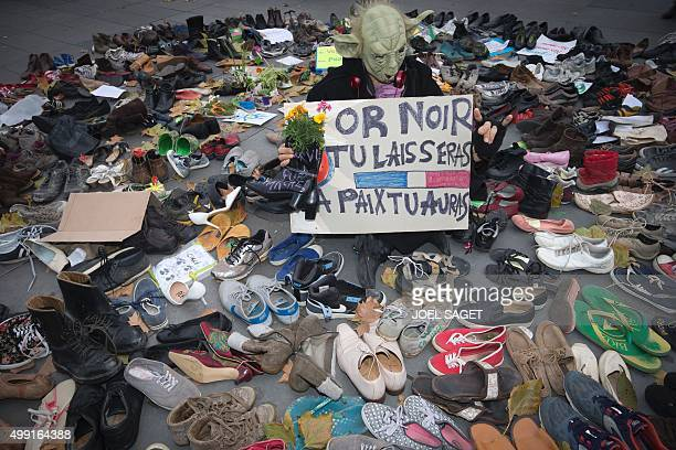 A man dressed as Yoda stands among shoes on the Place de la Republique which is covered in pairs of shoes on November 29 2015 in downtown Paris as...