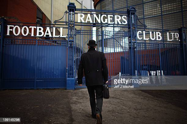 A man dressed in a bowler hat carrying a briefcase walks towards the Ibrox Stadium gates on February 17 2012 in Glasgow Scotland Rangers face...