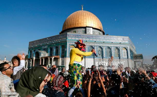A man dressed in a clown outfit distributes balloons to children as confetti is thrown by the Dome of the Rock inside alAqsa Mosque compound in...