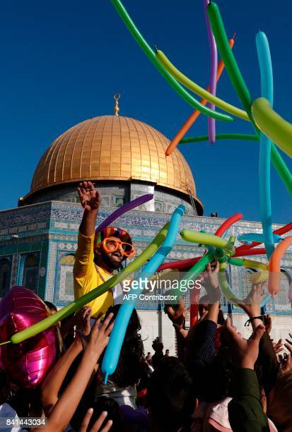 A man dressed in a clown outfit distributes balloons to children by the Dome of the Rock inside alAqsa Mosque compound in Jerusalem's old city on the...