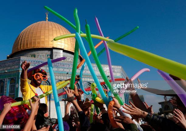 TOPSHOT A man dressed in a clown outfit distributes balloons to children by the Dome of the Rock inside alAqsa Mosque compound in Jerusalem's old...
