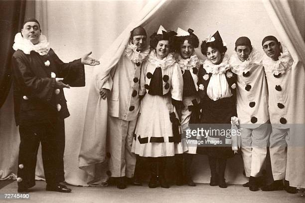 A man dressed in a dark clown suit with white details gestures as to introduce a group of three men and three women who emerge from behind a curtain...