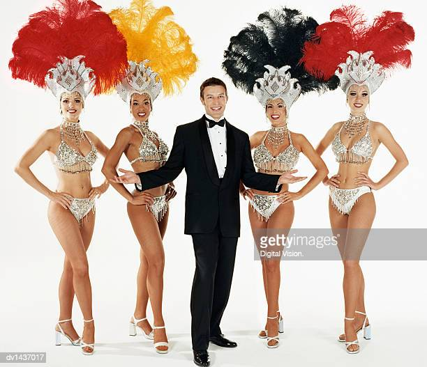 Man Dressed in a Dinner Jacket Standing Between Four Chorus Girls