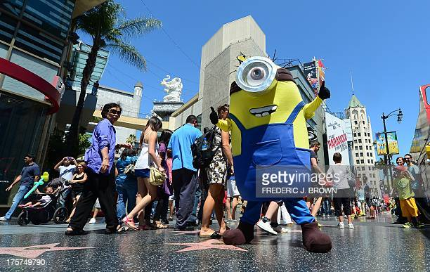 A man dressed in a Minion costume from the 'Despicable Me' movies strikes a pose along Hollywood Boulevard as tourists walk by on August 7 2013 in...