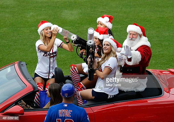 A man dressed in a Santa Claus outfit in a car driven by Braves cheerleaders waves to first base coach Brandon Hyde of the Chicago Cubs during...