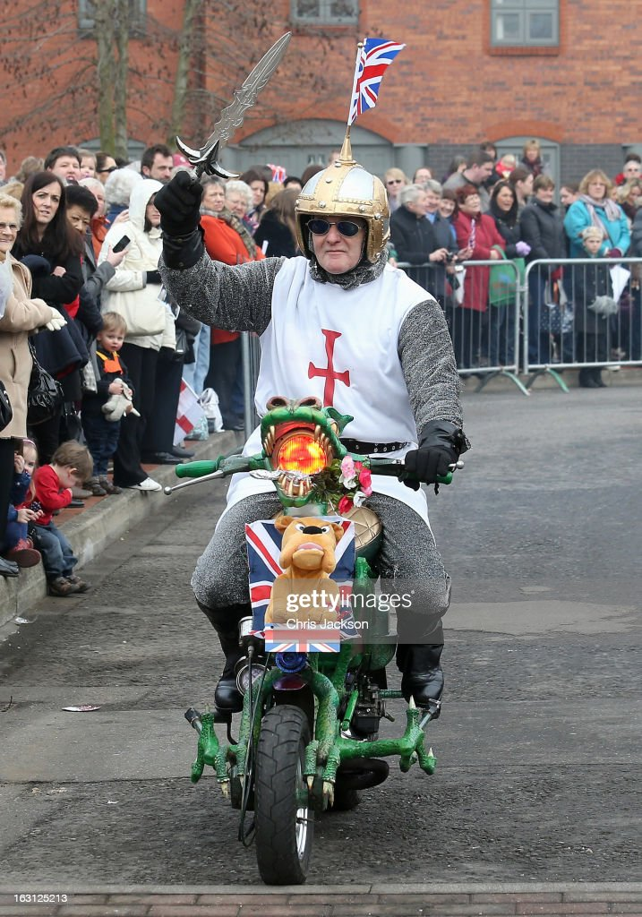 A man dressed in a St George costume rides past crowds waiting for the arrival of Catherine, Duchess of Cambridge on a motocycle decorated as a dragon at the National Fishing Heritage Centre on March 5, 2013 in Grimsby, England. The pregnant Duchess of Cambridge is spending the day visiting Grimsby in the North East of England.