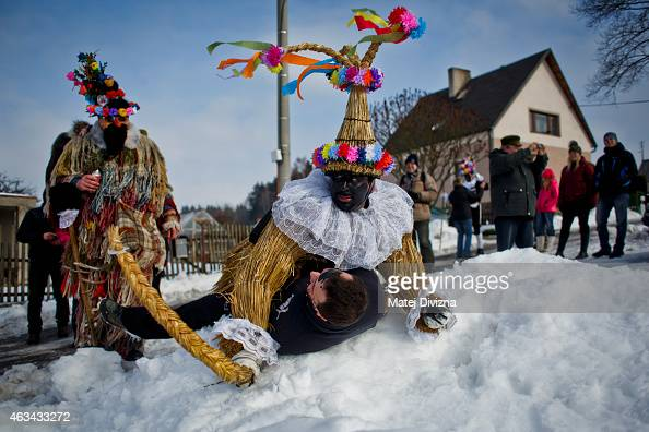 A man dressed in a traditional carnival costume and local man enjoy the traditional folklore carnival parade on February 14 2015 in Vortova Czech...