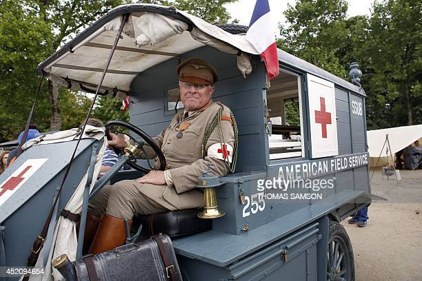 A man dressed in a US medic military World War I uniform sits in a WWI US ambulance at a WWI military camp reconstitution in the Tuilleries Garden in...