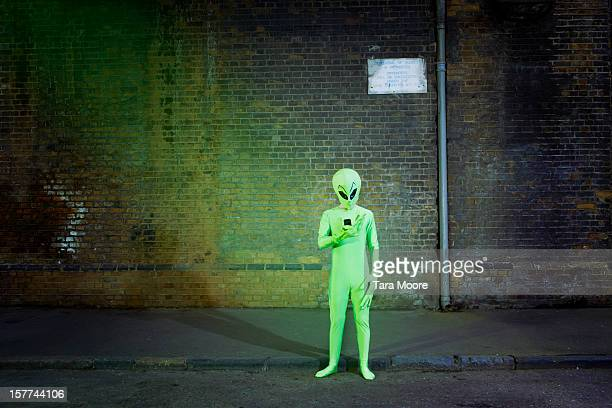 man dressed in alien costume looking at mobile