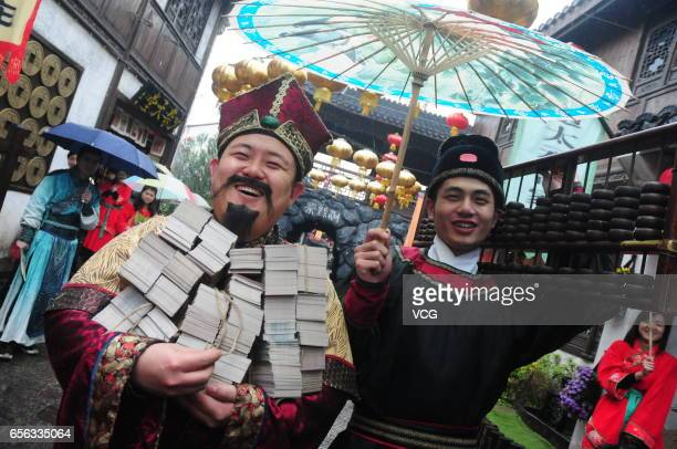 A man dressed in ancient costume holds ancient paper currency which will be distributed to working staff as their bonus at Hangzhou Songcheng scenic...