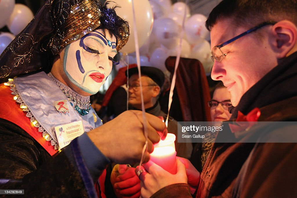 A man dressed in drag lights a candle for marchers mourning the victims of AIDS on November 30, 2011 in Berlin, Germany. Several hundred people, mostly members of the city's gay community, participated in the march one day ahead of World AIDS Day.