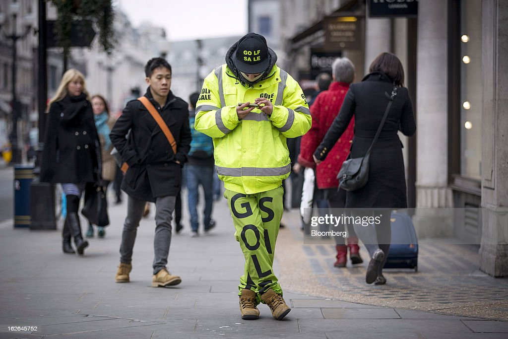 A man dressed in fluorescent green clothing advertises goods for sale at a Golf store as he stands on Regent Street in central London, U.K., on Monday, Feb. 25, 2013. U.K. Chancellor of the Exchequer George Osborne won't bow to opposition calls to change economic plans after the decision by Moody's Investors Service to strip the U.K. of its Aaa status. Photographer: Jason Alden/Bloomberg via Getty Images
