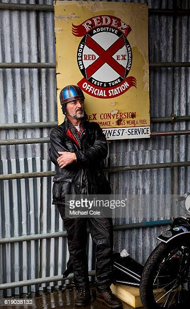 Man dressed in motorcycle outfit standing in front of large Redex enamel sign at Goodwood on September 10 2016 in Chichester England