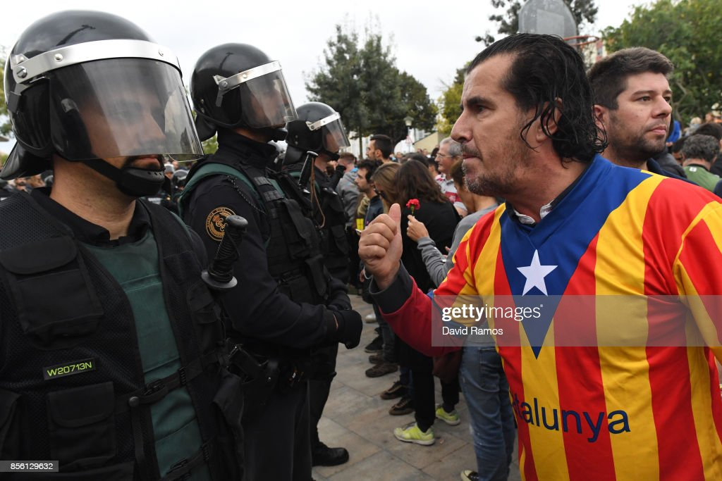 A man dressed in the Catalonian flag confronts officers as police move in on the crowds as members of the public gather outside to prevent them from stopping the opening and intended voting in the referendum at a polling station where the Catalonia President Carles Puigdemont will vote later today on October 1, 2017 in Sant Julia de Ramis, Spain. More than five million eligible Catalan voters are estimated to visit 2,315 polling stations today for Catalonia's referendum on independence from Spain. The Spanish government in Madrid has declared the vote illegal and undemocratic.