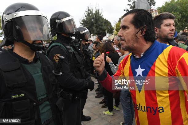 A man dressed in the Catalonian flag confronts officers as police move in on the crowds as members of the public gather outside to prevent them from...