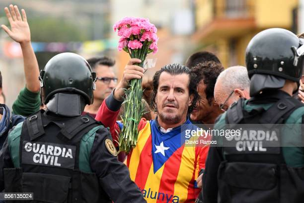 A man dressed in the Catalonian flag holds up pink flowers as police move in on the crowds gathered outside to prevent them from stopping the opening...