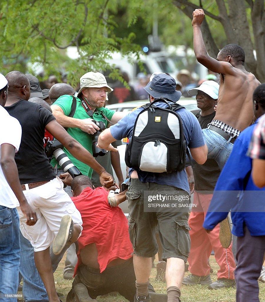 A man (Bottom L) dressed in the red color of the Congress of South African Trade Unions (Cosatu) is beaten up by striking miners as South African police officers fire rubber bullets, stun grenades and tear gas to disperse miners who were trying to prevent a rally organised by the Congress of South African Trade Unions (Cosatu) in Rustenburg, northwest of Johannesburg on October 27, 2012. Bullet casings littered the ground and a helicopter circled above, with police sirens howling, as the protesters were chased into the area surrounding the stadium. The clashes came a day after the National Union of Mineworkers (NUM) announced that it had reached a deal with the world's number one platinum producer Amplats to rehire 12,000 workers who were fired for a wildcat strike. Striking workers are disagree with the deal, which would signal a further winding down of a wave of wildcat strikes that have rocked platinum and gold mines since August.