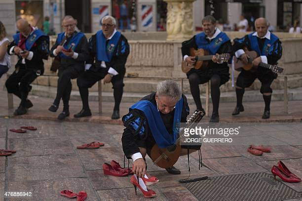A man dressed in traditional 'tuno' costume places a pair of red shoes at the Constitucion square in Malaga where the Mexican artist Elina Chauvet's...