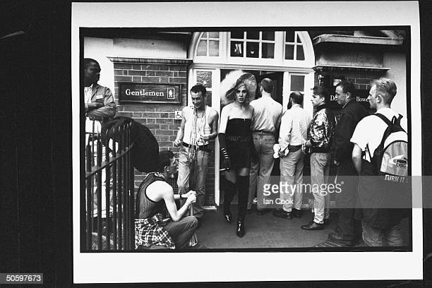 Man dressed in womens clothing standing nr line of men waiting to get into the Coleherne a gay pub that murder victims Peter Walker Emanuel Spiteri...