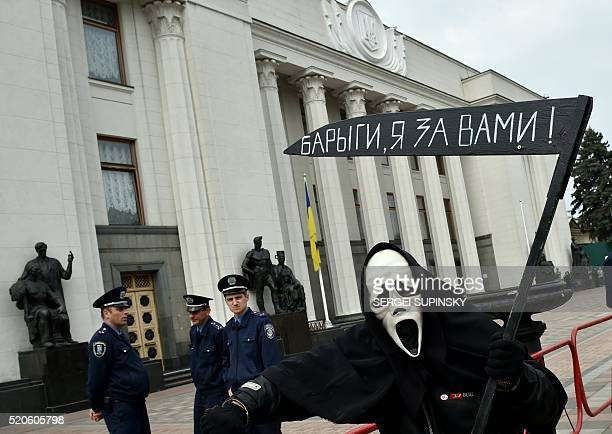 A man dressed up a the Reaper holds a scythe reading 'Petro Arseniy and Volodymyr go' and 'Hucksters I came for you' during a protest in front of the...