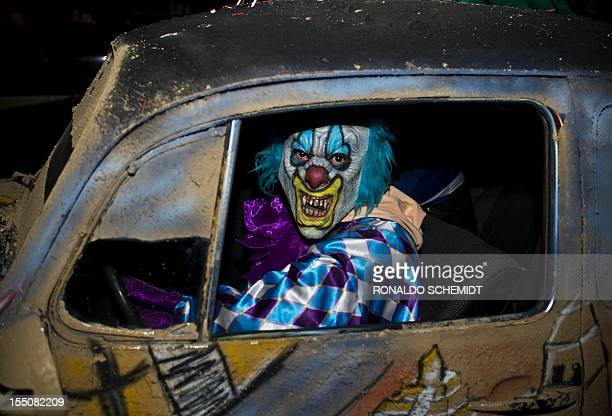 A man dressed up as a clown drives a car during the Halloween night on October 31 2012 in Mexico city AFP PHOTO / RONALDO SCHEMIDT