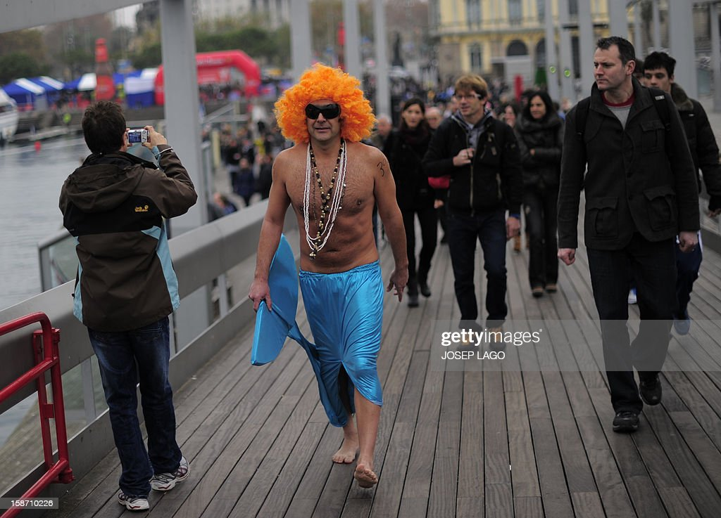 A man dressed up as a mermaid arrives to take part in the103rd edition of the Copa Nadal (Christmas Cup) at Barcelona's Port Vell on December 25, 2012. The traditional 200-meter Christmas swimming race gathered around 400 participants at the Old Harbour of Barcelona.