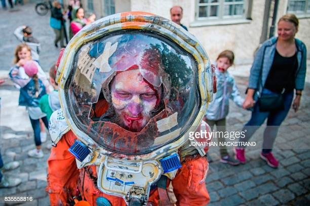 A man dressed up as a zombie astronaut participates in a zombie walk in Stockholm on August 19 2017 / AFP PHOTO / Jonathan NACKSTRAND