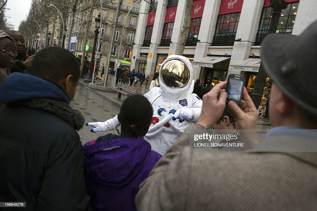 A man dressed up as an astronaut poses on the Champs-Elysees avenue on January 4, 2013 in Paris.