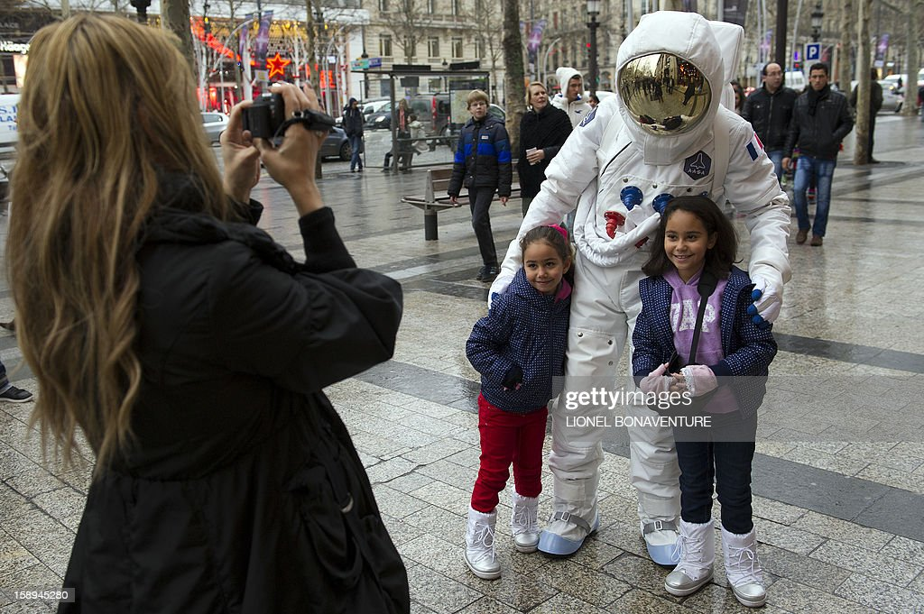 A man dressed up as an astronaut poses with children on the Champs-Elysees avenue on January 4, 2013 in Paris. AFP PHOTO / LIONEL BONAVENTURE