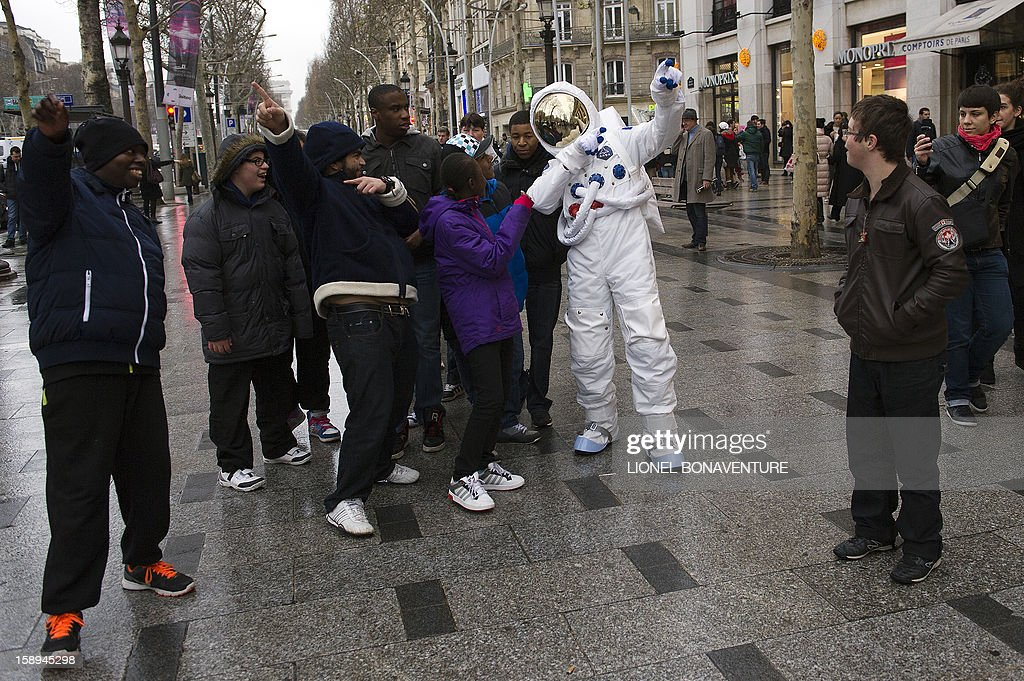 A man dressed up as an astronaut poses with teenagers on the Champs-Elysees avenue on January 4, 2013 in Paris.