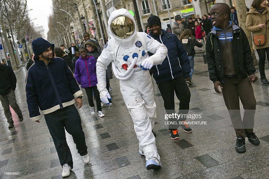 A man dressed up as an astronaut walks down the Champs-Elysees avenue on January 4, 2013 in Paris.
