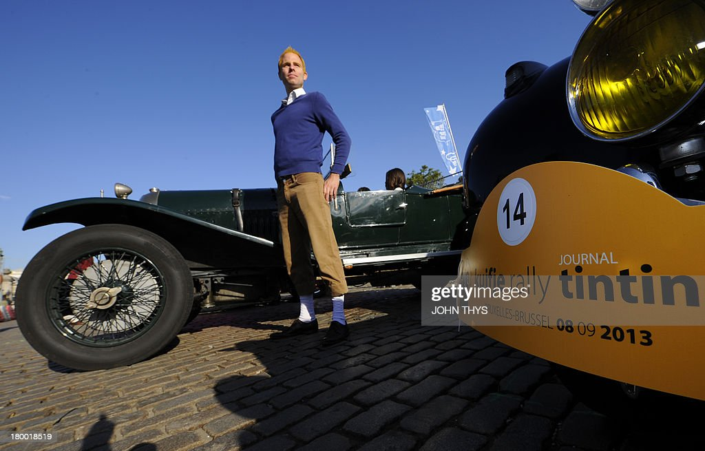 A man dressed up as comic book character Tintin poses next to a car of 'Tintin magazine' car rally on September 8, 2013 in Brussels. This unusual rally features real cars and motorbikes inspired by vehicles illustrated in the pages of Tintin's Diary at the occasion of Brussels' comic book festival.