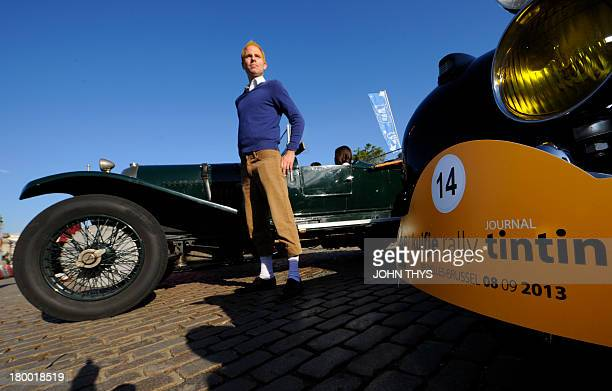 A man dressed up as comic book character Tintin poses next to a car of 'Tintin magazine' car rally on September 8 2013 in Brussels This unusual rally...