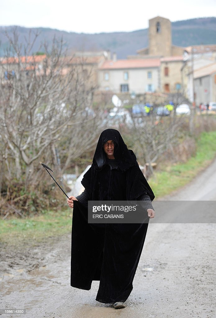 A man dressed up as the Death walks, on December 21, 2012 in a street of the French southwestern village of Bugarach, near the 1,231 meter high peak of Bugarach - one of the few places on Earth some believe will be spared when the world allegedly ends today according to claims regarding the ancient Mayan calendar. French authorities have pleaded with New Age fanatics, sightseers and media crews not to converge on the tiny village.