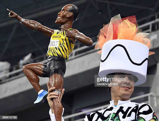 TOPSHOT A man dressed up as the Olympic Torch holds a figure representing Jamaica's Usain Bolt as he waits for the Men's 100m Final during the...