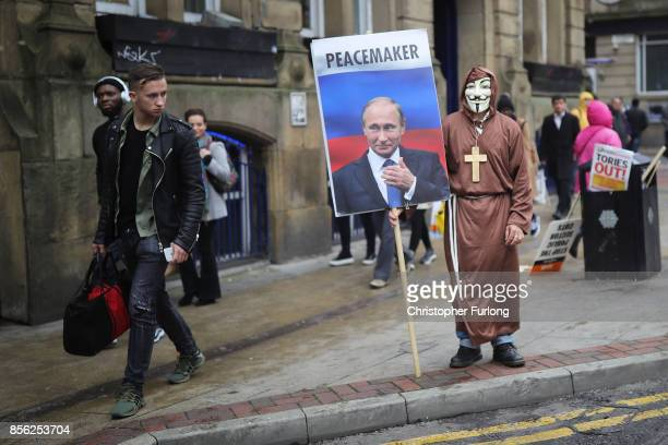 A man dressed up in a mask and holding a sign with Vladimir Putin on it saying 'Peacemaker' takes part in antiBrexit and antiausterity protests as...