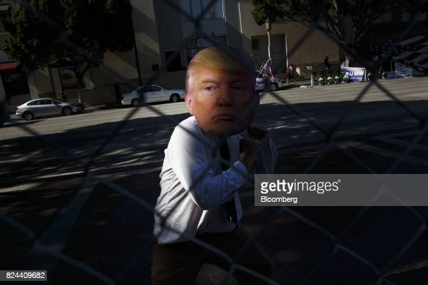 A man dressed with a mask of US president Donald J Trump stands outside a fence during the Politicon convention inside the Pasadena Convention Center...