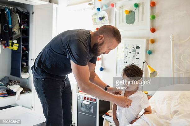Man dressing son in bedroom