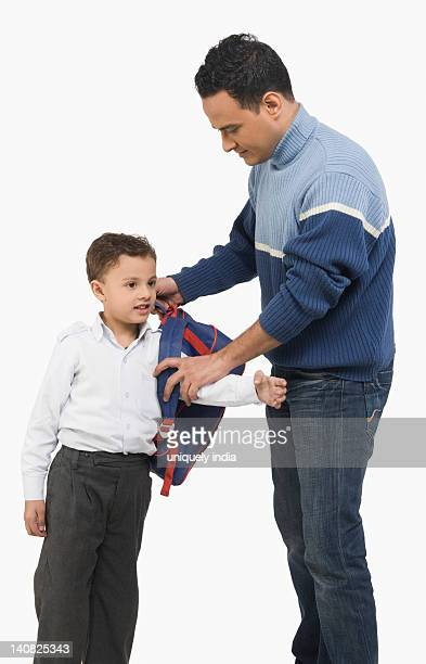 Man dressing up his son for school