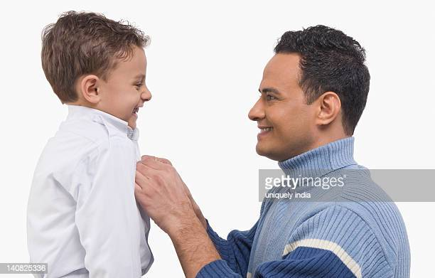 Man dressing up his son