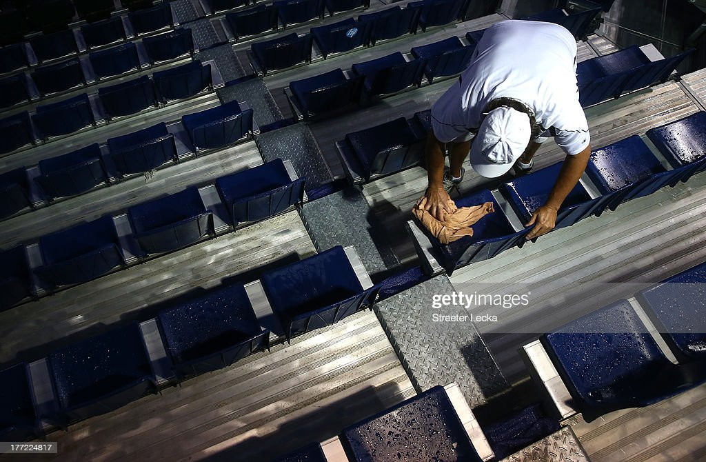 A man dries off seats in a rain delay of the quarterfinals matches during day 5 of the Winston-Salem Open at Wake Forest University on August 22, 2013 in Winston Salem, North Carolina.