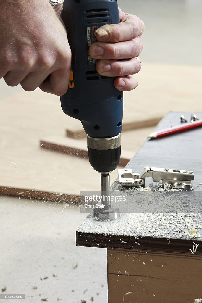 Man drilling a hole into a wood cabinet door