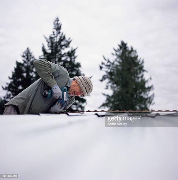 'Man drilling screws into metal roof, Vashon Island, Washington'