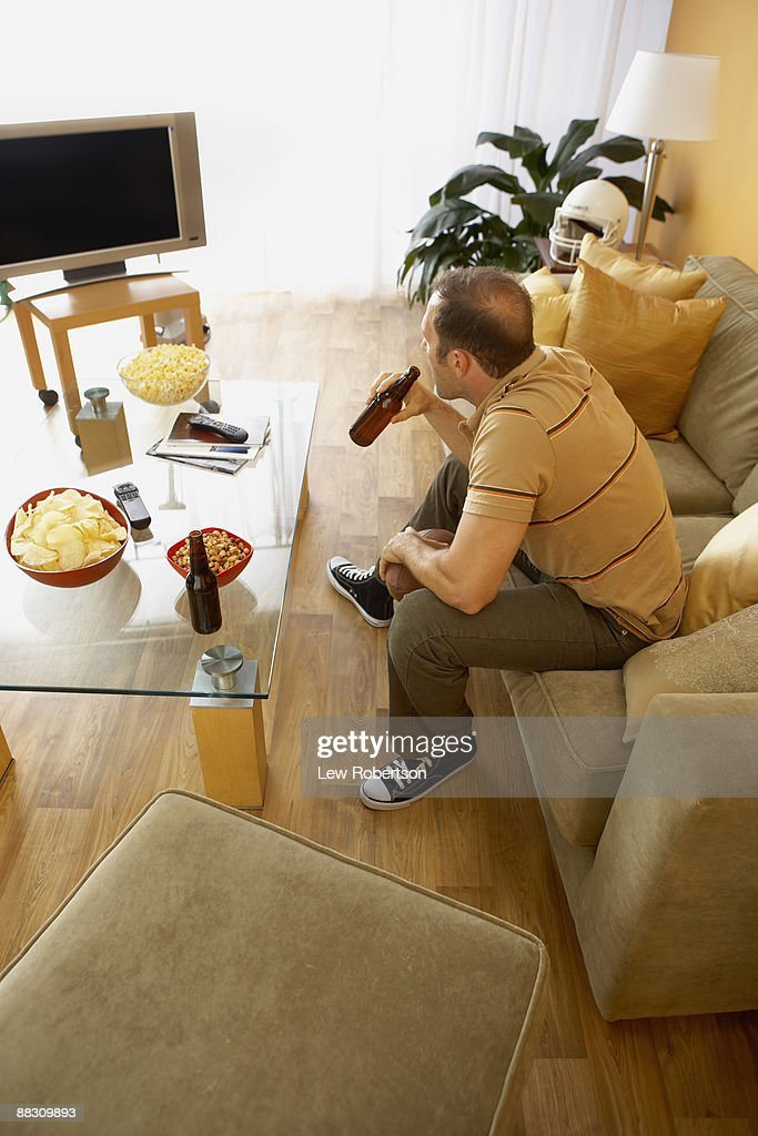 Man drinking a beer while watching television : Stock Photo