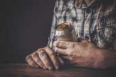 Man drinking a cold beer after work in the evening. Hand holding a aluminum can. Resting time in the bar or pub. Dark depressive atmosphere. Alcohol problem concept.