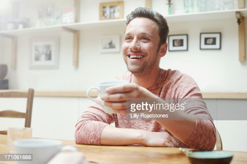 Man drinking at kitchen table in morning : Stock Photo