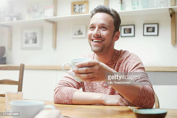 Man drinking at kitchen table in morning