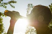 Man drinking beer from bottle in sunlight