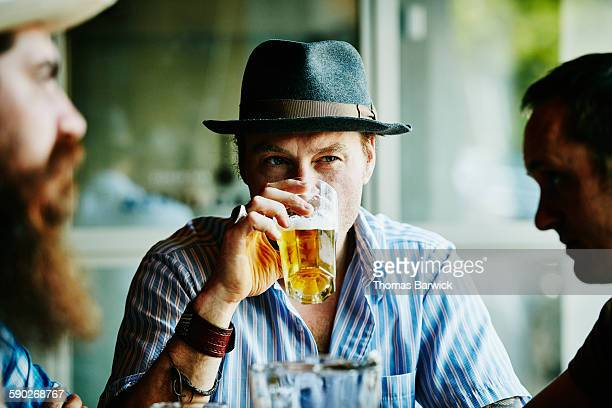 Man drinking beer in restaurant with friends