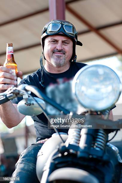 Man drinking beer on motorcycle